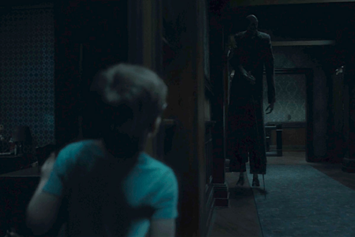 A movie frame showing a boy peeking out of his room and seeing a ghost of a tall man with a cane, stopped next door.